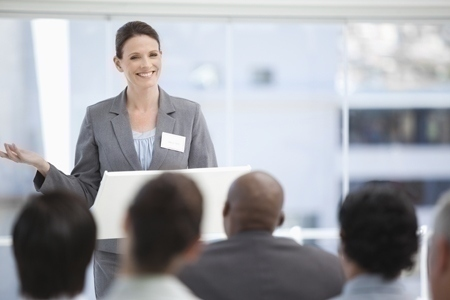 Smiling businesswoman gesturing with her hand as she is being watched by her colleagues with focus on the businesswoman