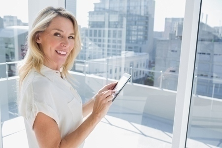 Smiling businesswoman touching her tablet computer in a bright office