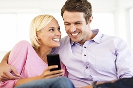 Couple Using Smart Phone Together At House