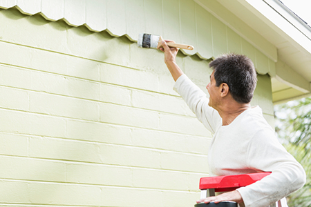 Hispanic man painting house