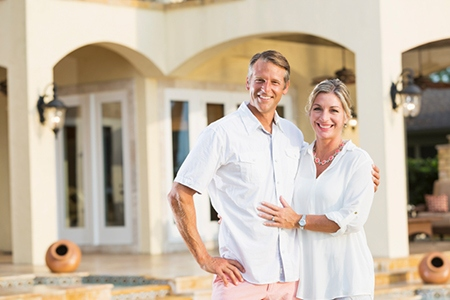 Wealthy mature couple outside their luxury home