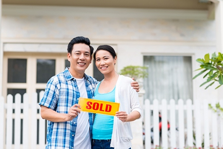 Middle-aged couple with sold sign