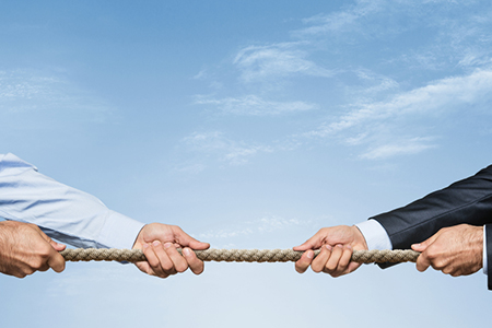 Tug war, two businessman pulling a rope in opposite directions o