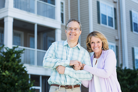 Mature couple in front of apartment building