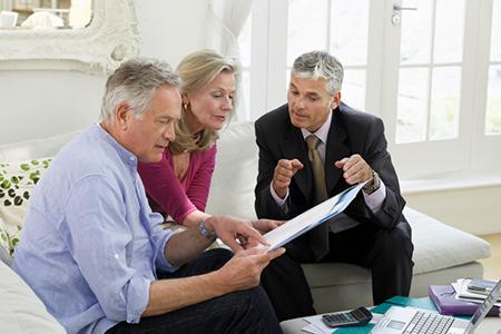 Couple With Financial Advisor At Sofa