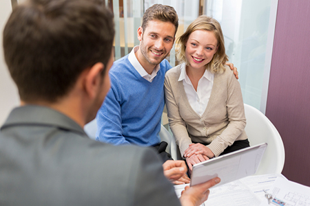 Young couple meeting real-estate showing a investment project on