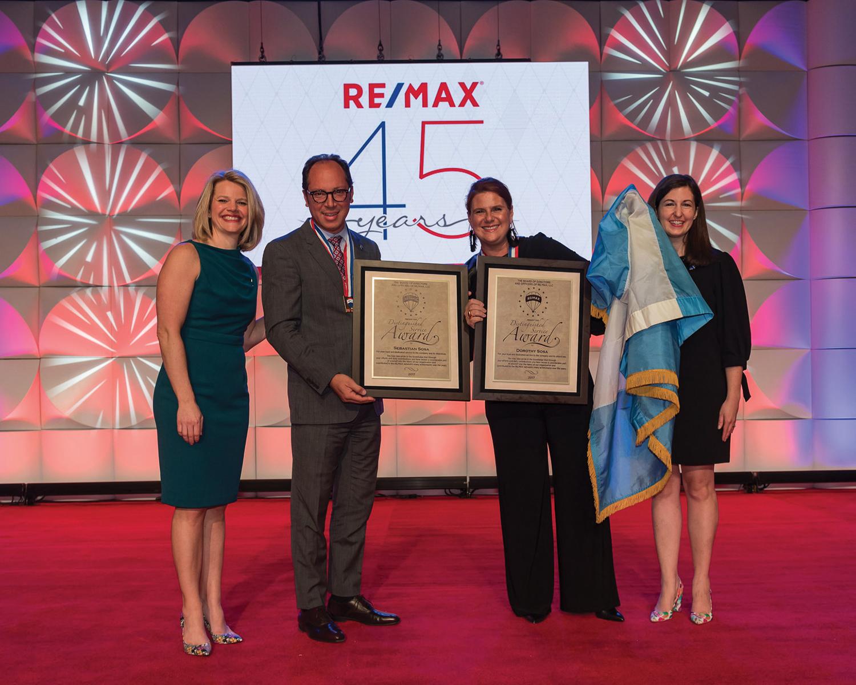 RE/MAX COO Serene Smith (L) and CFO Karri Callahan (R) present an award to global leaders Sebastian Sosa and Dotti Penate-Sosa.