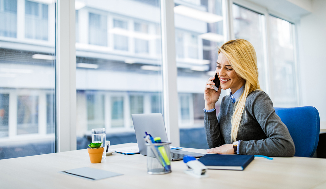 Happy Businesswoman Talking On Cell Phone While Working On